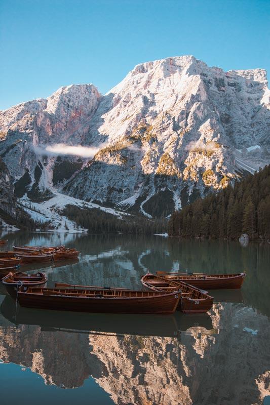 Boote liegen im Morgenlicht ruhig auf dem Pragser Wildsee