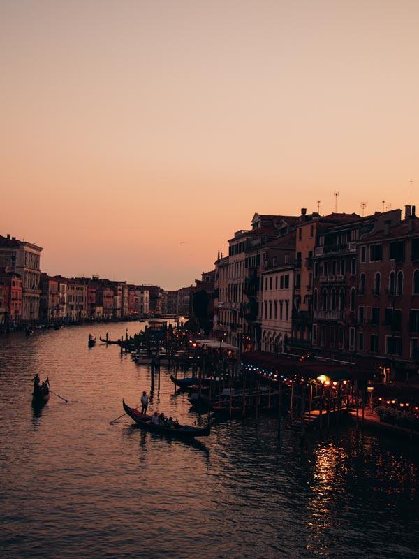 Blick auf Gondel im Canal Grande von der Rialtobrücke, während hinter den Dächer von Venedig die Sonne untergeht